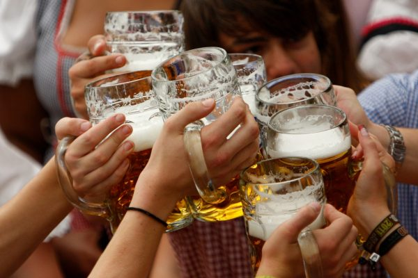 """Visitors lift their beer mugs in the Hofbraeuhaus-tent after the opening of the famous Bavarian """"Oktoberfest"""" beer festival in a beer tent in Munich, southern Germany, on Saturday, Sept.17, 2011."""